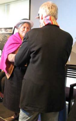 An elder from Ecuador gives James Cameron a handmade textile after the