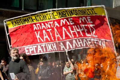 "SOLIDARITY: Protesters in Athens carry a banner that reads ""Shut Downs — Sackings — Privatizations; We Respond with Occupations,"" and is signed by ""Worker's Solidarity."" PHOTO: FIL KALER, FILKALER.COM"