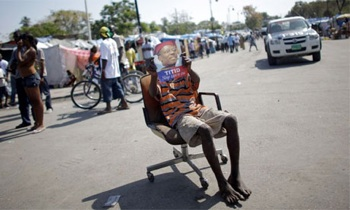 A boy holds a picture of the ousted former president of Haiti, Jean-Bertrand Aristide, as he sits on a chair outside the presidential palace during a visit by France's President Nicolas Sarkozy to Port-au-Prince, in February 2010, in the wake of the earthquake. Photograph: Carlos Barria/Reuters