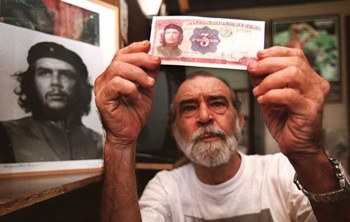 Alberto Korda in front of his famous snapshot Guerrillero Heroico, and holding a 3 Cuban Peso banknote, which also bears his photo. PHOTO: WIKIMEDIA COMMONS.