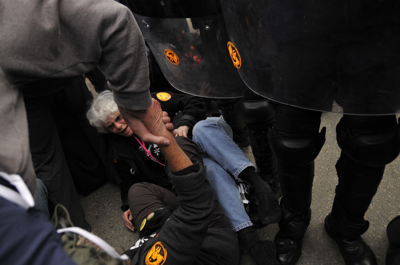 Police almost trample protesters sitting in the road at Quantico Marine base. Photo by ELLEN DAVIDSON