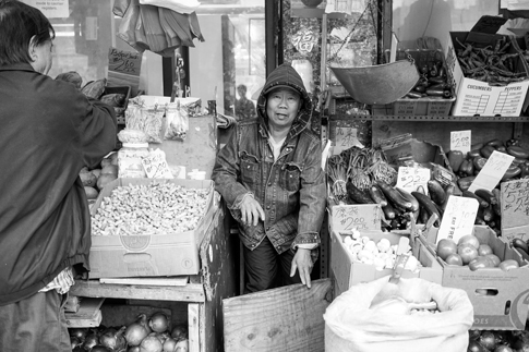 A grocery store worker sells fruit and vegetables.