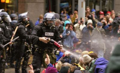 WHAT A BLAST: A Seattle police officer fires pepper spray into a line of seated protesters. The authorities were unprepared for the WTO demonstrators' creative, decentralized tactics. PHOTO: FLICKR.COM/PHOTOS/DJBONES