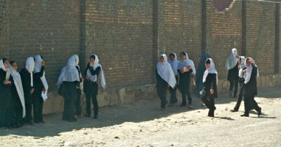 AGAINST THE WALL: While life has improved for some women, such as these schoolgirls in Kabul, for most women their situation has deteriorated since the U.S.-led invasion began. Just like under the Taliban, women remain prisoners in their homes, but now they suffer the brunt of the war. PHOTO: FLICKR.COM/MICHAEL FOLEY. This photo was published under creative commons licensing.