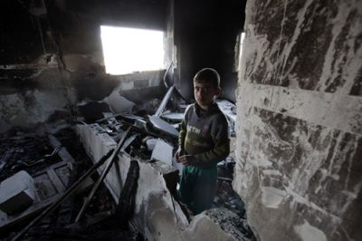 CHILDHOOD HOME: Nine-year-old Abdullah Samouni stands in the wreckage of his home in March 2009 in the Zeitoun neighborhood of Gaza City. During the 2009 invsation of Gaza, Israeil forces ordered his family to move to a different home, which the Israeli military subsequently shelled, killing 30 family members. Israel's assault destroyed or severely damaged 15,000 homes, rendering 100,000 Gazans homeless. PHOTO: JESSIE BOYLAN