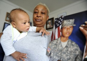 Angelique Hughes holds her grandson, Kamani, who looks at a photo of his mother, Specialist Alexis Hutchinson.