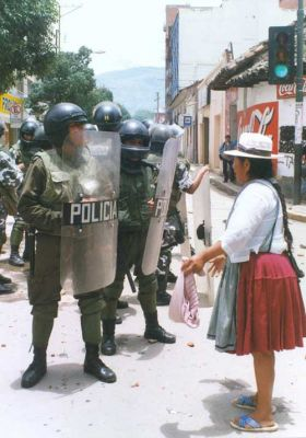DRINK THIS: A Bolivian woman confronts police during the April 2000 water revolt in Cochabamba. PHOTO: TOM KRUSE