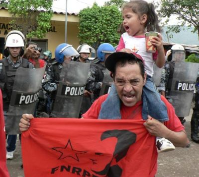 NOT AFRAID: A member of the Honduran National Front of Popular Resistance (FNPR) carries his daughter as they march past a line of police special forces. PHOTO: GIORGIO TRUCCHI/Rel-UITA