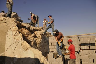 Human chains transported buckets of concrete to the workers  pouring it into the forms. PHOTO: ELLEN DAVIDSON