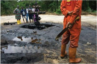 A Shell worker holds a machete during a clean-up operation of an oil spill in Oloibiri, while disgruntled locals watch. In one incident in 2004, more than 800,000 gallons of crude gushed out of an old wellhead, fouling Oloibiri.