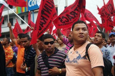 A SEA OF RED FLAGS: Construction workers march against the Chorizo Law. PHOTO: ERIC JACKSON