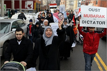 Ahmed Rashed (left) and his wife Shaimaa Badr (right) marched with protesters against Egyptian President Hosni Mubarak's regime down Massachusetts Avenue in Cambridge. PHOTO: Jonathan Wiggs/Globe Staf