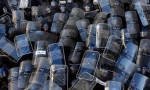 Riot police use their shields during a demonstration in Algiers last month. PHOTO: AP