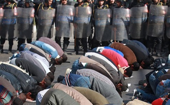 Locals pray in the street in front of The l-Istiqama Mosque watched by riot police in Cairo, Egypt.  Photo: Getty Images/Peter Macdiarmid