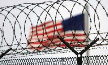 A US flag waves within the razorwire-lined compound of Camp Delta prison at Guantánamo Bay in 2006. PHOTO: Brennan Linsley/Pool/Reuters