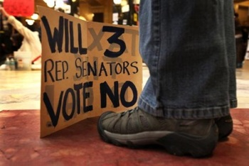 A protester and his sign in the capitol rotunda in Madison, Wis., on March 1, 2011. PHOTO: Scott Olson/Getty Images