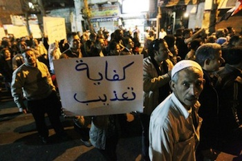 An Egyptian man walks past a banner reading in Arabic 'enough tortures' as people demonstrate against military trials and call for reforms during a march from to the Prime minister office in downtown Cairo on March 27, 2011.   (KHALED DESOUKI/AFP/Getty Images)