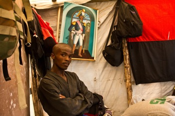 A young recruit in the would-be Haitian army stands in a changing room with a portrait of revolutionary leader Henri Christophe and the Duvalier party red-and-black flag behind him. PHOTO: Isabeau Doucet