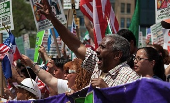 Protesters wave flags and chant at the 2010 May Day rally in New York City. PHOTO: Creative Commons/Jens Schott Knudsen