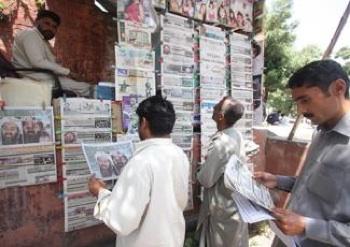 Pakistani men reading papers about Osama bin Laden's killing. PHOTO: T Mughal/EPA