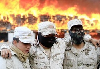 Mexican soldiers at a base in Tijuana pose for pictures while they burn the biggest pot seizure in Mexican history last fall. The drug policy panel recommended that narcotics be legalized and regulated, especially marijuana. PHOTO: Mark Boster, Los Angeles Times / October 20, 2010