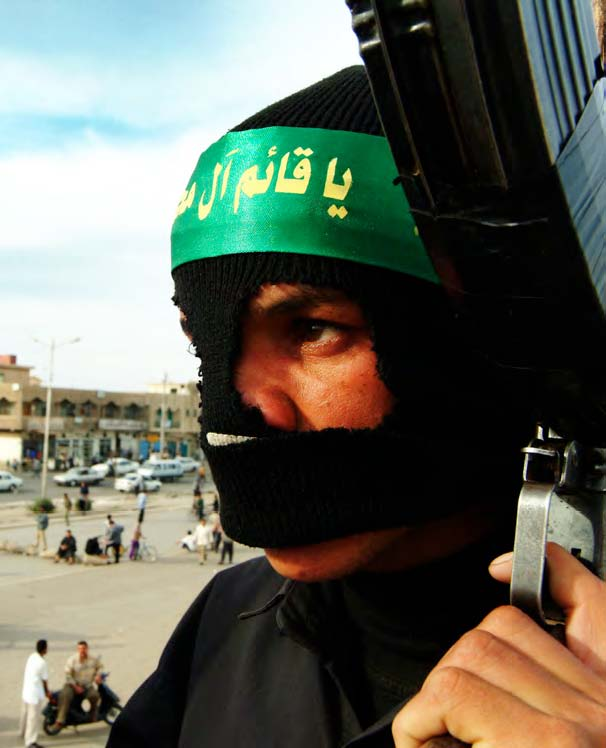 A member of the Mahdi Army watches over Sadr City in 2004. The Shiite paramilitary group played a key role in Iraq's civil war before it was demobilized in 2008. (Photo: Rick Rowley)