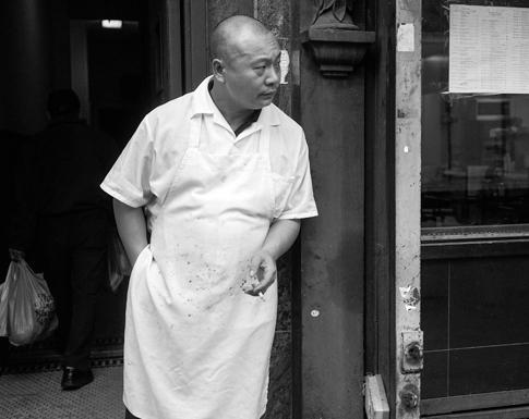 A man in an apron takes a cigarette break. Photo: Cynthia Trinh