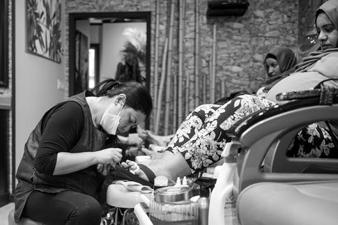 A nail salon worker paints a client's toenails.