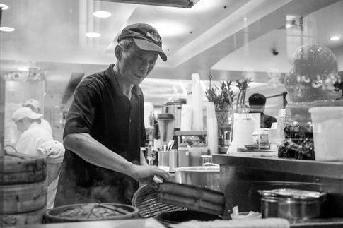 An elderly man works in a restaurant kitchen.